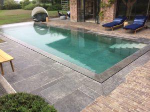 Zwembad in zichtbeton met aangrenzende poolhouse en jacuzzi